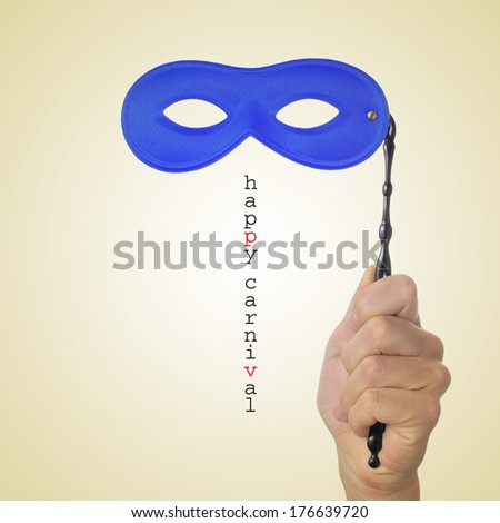 sentence happy carnival and a man hand holding a blue carnival mask on a beige background, with a retro effect - stock photo