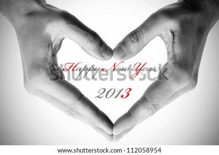 sentence happy new year 2013 and hands forming a heart - stock photo
