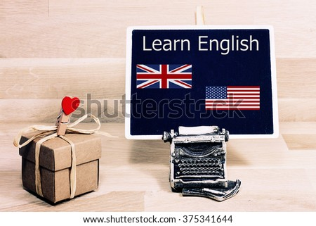 sentence learn english written with chalk on a blackboard, on a table with typewriter, American flag and England flag