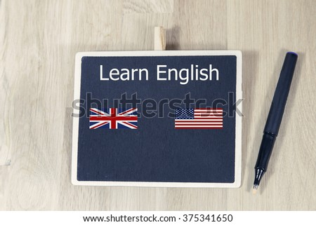 sentence learn english written with chalk on a blackboard, on a table with typewriter. American flag and England flag
