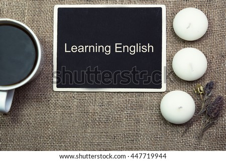 sentence Learning English written with chalk on a blackboard, on a table with pen.coffee.coffee cup. - stock photo