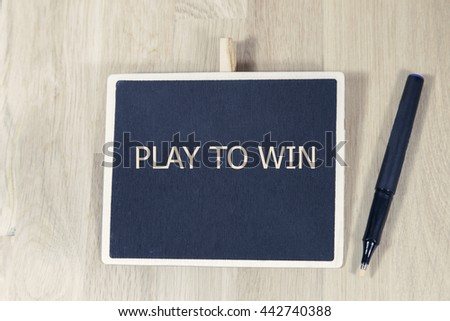 sentence play to win written with chalkboard on a wooden table with pen. - stock photo