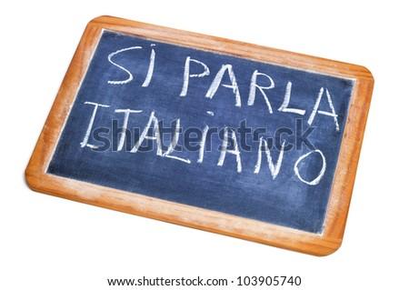sentence si parla italiano, italian is spoken, written on a chalkboard - stock photo