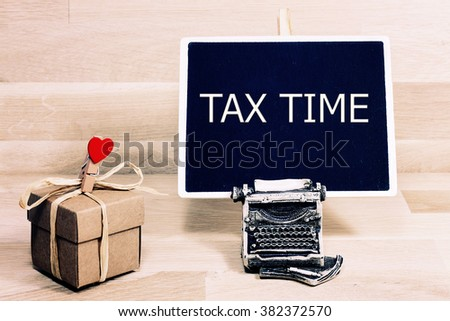 sentence  tax time written with chalk on a blackboard, on a table with typewriter - stock photo