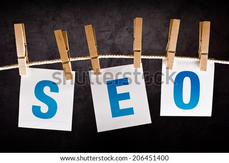 SEO concept, search engine optimization. Letters printed on notes paper hanging on rope. - stock photo
