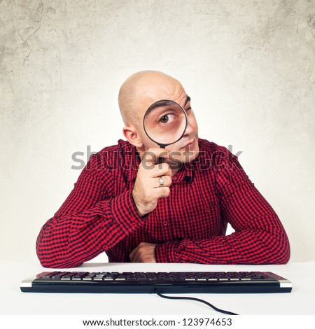 SEO expert at computer table holding magnifying glass in front of the monitor, internet search concept