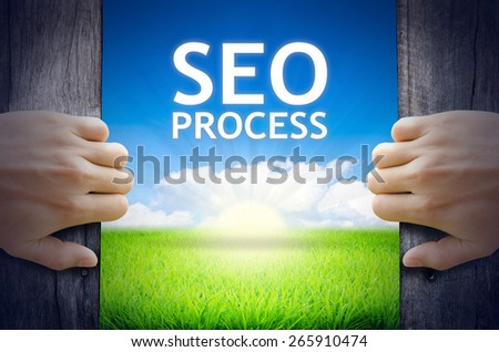 SEO Process. Hands opening a wooden door then found a texts floating among new world as green grass field, Blue sky and the Sunrise. - stock photo