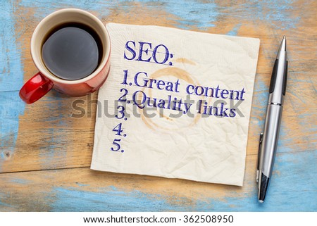 SEO (search engine optimization) tips (great content and quality links) on napkin with a cup of coffee - stock photo