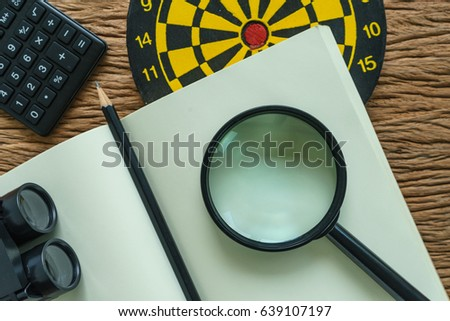 SEO (search engine optimization) website promotion concept with pencil, dart, magnifying glass and binoculars in flat lay.