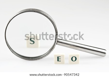 SEO word and magnifying glass - stock photo
