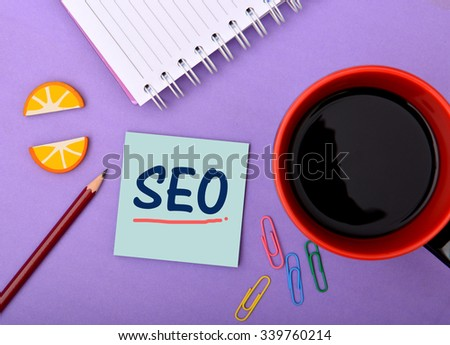 SEO written on notepad Closeup with Cup of Tea - stock photo