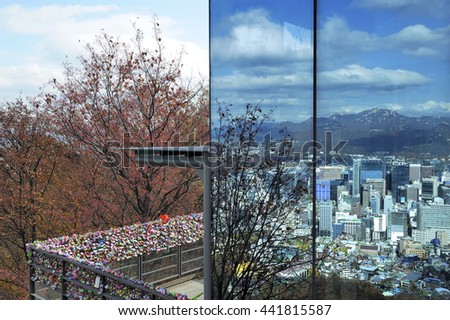 Seoul city in daylight reflected in the windows of Seoul Tower with at left love padlocks, Seoul, South Korea.