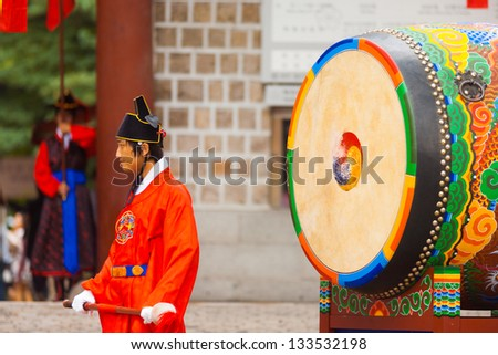 SEOUL, KOREA - AUGUST 27, 2009: A traditional Korean drummer in period costume waits to bang an ancient drum at Deoksugung Palace, a tourist landmark, in Seoul, South Korea on August 27, 2009 - stock photo