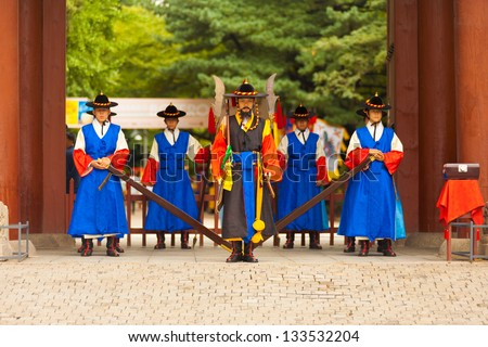 SEOUL, KOREA - AUGUST 27, 2009: Armed guards in traditional costume stand at the entry gate of Deoksugung Palace, a tourist landmark, in Seoul, South Korea on August 27, 2009 - stock photo