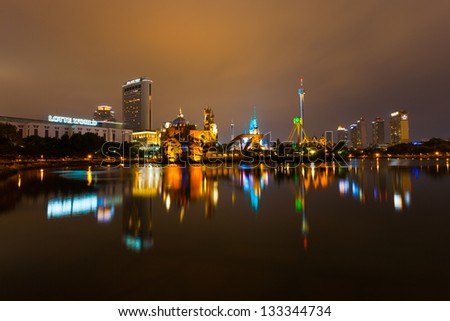 SEOUL, KOREA - AUGUST 26, 2009: The lights of Lotte World, a Korean amusement park and major tourist destination, reflect from the surface of a lake at night in Seoul, South Korea on August 26, 2009 - stock photo