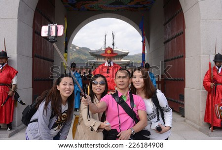 SEOUL, KOREA - OCTOBER 22 : Tourists selfie with mobile phone in front of Gyeongbokgung Palace in Seoul, Korea on October 22, 2014 - stock photo