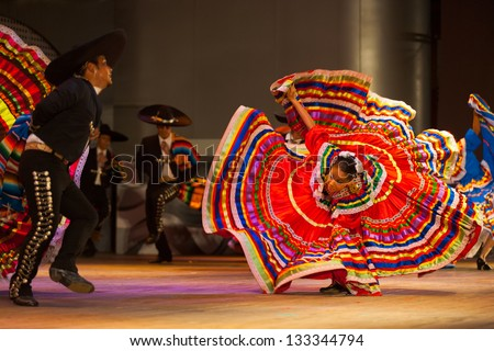 Seoul, Korea - September 30, 2009: Female Mexican Jalisco dancer bent over in fluttering orange dress spinning, twirling at a folkloric dance outdoor free performance in Seoul, South Korea
