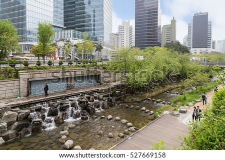 SEOUL, SOUTH KOREA - APRIL 21, 2016: Artificial waterfall and people along the Cheonggyecheon Stream and modern office buildings in Seoul, South Korea.