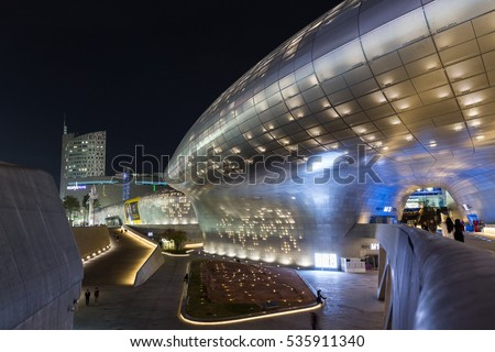 SEOUL, SOUTH KOREA - APRIL 19, 2016: Plaza, bridge and side view of the futuristic Dongdaemun Design Plaza (DDP) in Seoul, South Korea at night.