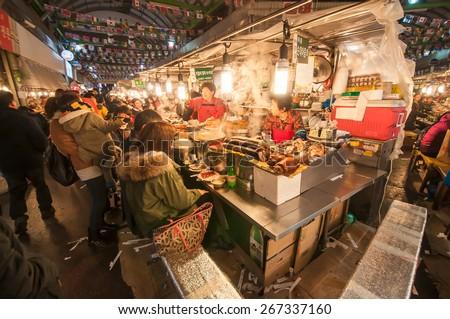 SEOUL, SOUTH KOREA - FEBRUARY 28, 2015 : People enjoying street food at Gwangjang Market.The market was established in 1905 .It has many restaurants and food stalls selling traditional Korean cuisine. - stock photo