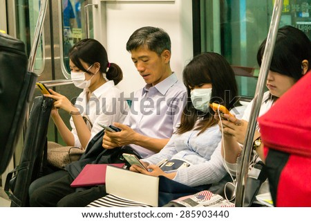 SEOUL, SOUTH KOREA - JUN 10, 2015: Passengers on the subway wear masks to protect against the deadly MERS (Middle East Respiratory Syndrome) virus outbreak in Korea. - stock photo