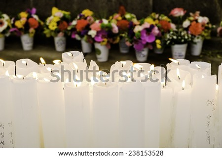 SEOUL, SOUTH KOREA - MARCH 11, 2014: An array of white candles burning on an altar in the historic landmark Bongeunsa Buddhist temple with flower offerings arranged in the background. - stock photo