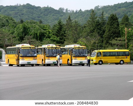 SEOUL, SOUTH KOREA - MAY 31: South Korean School Buses in parking lot. The School Bus transport the student body population to and from school.   Seoul, South Korea, May 31, 2005. - stock photo