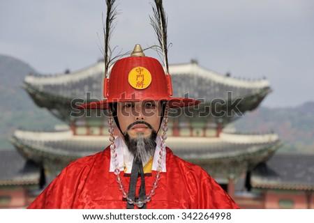 SEOUL, SOUTH KOREA - NOVEMBER 11, 2015: Armed guard in traditional costume guard the entry gate at Deoksugung Palace, a tourist landmark, in Seoul. November 11, 2015 Seoul, South Korea - stock photo