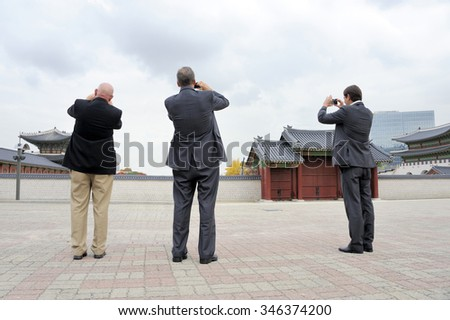 SEOUL, SOUTH KOREA-NOVEMBER 10:Three men making a photo of Gyeongbokgung Palace. At Left in the background the Head Office of Microsoft in South Korea.November 10, 2015 Seoul, South Korea - stock photo