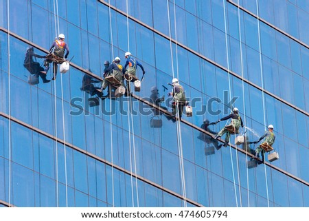 Seoul, South Korea - October 25, 2014: Laborers clean windows as a team on a skyscraper in downtown Seoul, South Korea