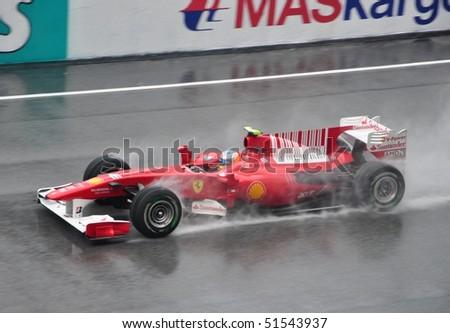 SEPANG F1 CIRCUIT, MALAYSIA - APR 3 : Scuderia Ferrari Marlboro driver Fernando Alonso  speeding on wet track during qualifying session on April 3, 2010 in Sepang F1 Circuit, Malaysia - stock photo