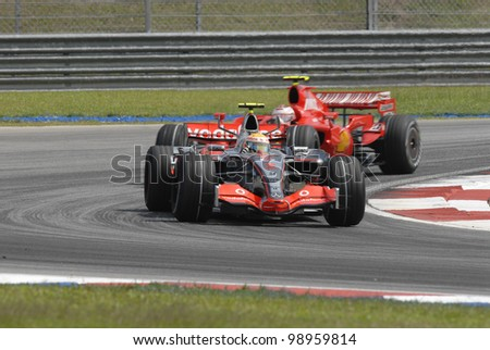 SEPANG, MALAYSIA-APR 8:F1 driver Lewis Hamilton leads Kimi Raikkonen during Petronas Malaysian Grand Prix in Sepang, Malaysia on April 8, 2007. Fernando Alonso of McLaren Mercedes won the race - stock photo