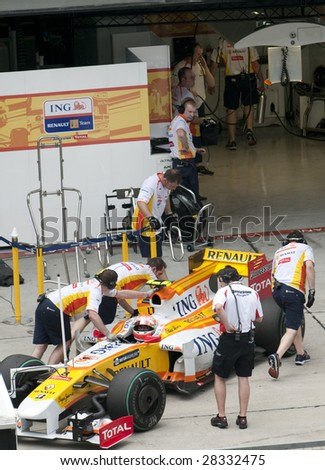 SEPANG, MALAYSIA - APRIL 3: Mechanics push Nelson Piquet Jr.'s car of ING Renault F1 Team during practice session at Malaysian F1 Grand Prix April 3, 2009 at Sepang International Circuit in Sepang. - stock photo