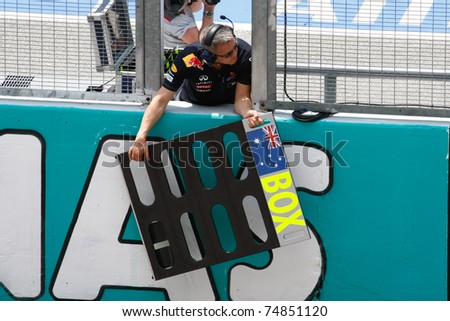 SEPANG, MALAYSIA - APRIL 8: Red Bull Racing's crew prepares to send a message to Mark Webber on the first practice day of the Petronas Malaysian F1 Grand Prix on April 8, 2011 in Sepang, Malaysia. - stock photo
