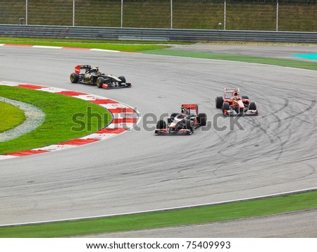 SEPANG, MALAYSIA - APRIL 10: Unidentified racers round one of the curves on the track at the Formula 1 GP race on  April 10 2011 in  Sepang, Malaysia