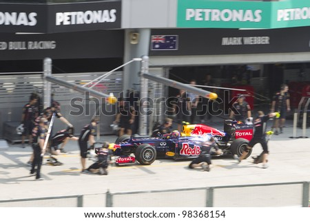 SEPANG, MALAYSIA - MARCH 23: Australian Mark Webber of Team Red Bull does a trial pit stop during Friday practice at Petronas Formula 1 Grand Prix March 23, 2012 in Sepang, Malaysia - stock photo