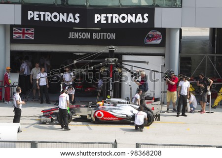 SEPANG, MALAYSIA - MARCH 23: British Lewis Hamilton of Team McLaren does a trial pitstop during Friday practice at Petronas Formula 1 Grand Prix March 23, 2012 in Sepang, Malaysia - stock photo