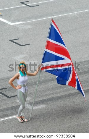 SEPANG, MALAYSIA - MARCH 25 : Grid girl holds the British flag during the opening ceremony of F1 Petronas Malaysian Grand Prix at Sepang F1 circuit on March 25, 2012 in Sepang, Malaysia - stock photo