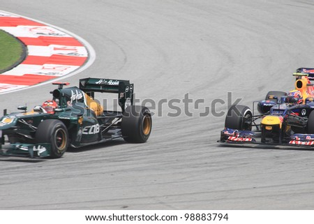 SEPANG, MALAYSIA - MARCH 23: Heikki Kovalainen of Caterham and Mark Webber of Red Bull Racing in action during Friday practice at Petronas Formula 1 Grand Prix on March 23, 2012 in Sepang, Malaysia - stock photo