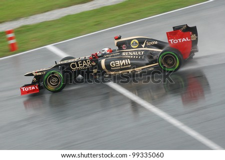 SEPANG, MALAYSIA - MARCH 25: Lotus-Renault F1 Team driver Kimi Raikkonen on wet track during race day of F1 Petronas Malaysian Grand Prix at Sepang F1 circuit on March 25, 2012 in Sepang, Malaysia - stock photo
