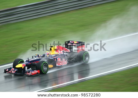 SEPANG, MALAYSIA - MARCH 25: Mark Webber of Red Bull Racing team in action during rain in Formula One PETRONAS Malaysian Grand Prix at Sepang F1 circuit on 25 March, 2012 in Sepang, Malaysia - stock photo