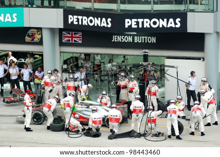 SEPANG, MALAYSIA - MARCH 25: McLaren Mercedes Team crews does pit-stop practice at the 2012 F1 Petronas Malaysian Grand Prix at Sepang International Circuit on March 25, 2012 in Sepang, Malaysia - stock photo