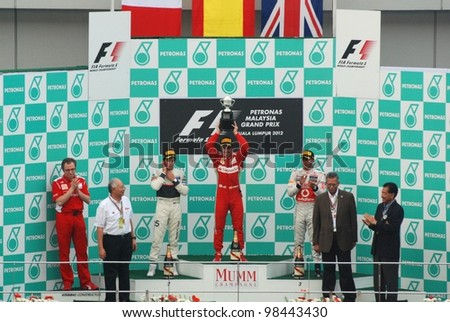 SEPANG, MALAYSIA - MARCH 25: Race winner Fernando Alonso of Ferrari F1 Team holding the trophy on podium  at F1 Petronas Malaysian Grand Prix on March 25, 2012 in Sepang, Malaysia