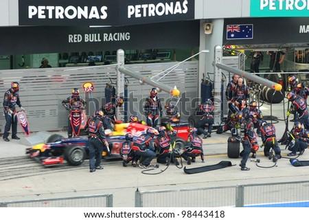 SEPANG, MALAYSIA - MARCH 25: Redbull Racing Team crews does pit-stop practice at the 2012 F1 Petronas Malaysian Grand Prix at Sepang International Circuit on March 25, 2012 in Sepang, Malaysia - stock photo