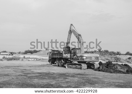 Sepang, Malaysia 14 May 2016, An excavator on a construction site against clear sky in black and white - stock photo