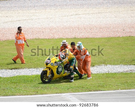 SEPANG, MALAYSIA - OCT. 21: Alex De Angelis of JIR Moto2 gets help after a crash during a practice session of the Shell Advance Malaysian Moto GrandPrix on Oct. 21 2011 in Sepang, Malaysia. - stock photo