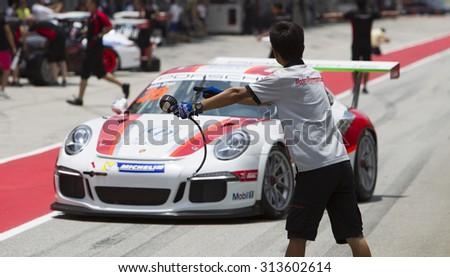 Sepang, Malaysia - September 5, 2015 : Canadian John Shen of Team Modena Motorsports directed into pit at Porsche Carrera Cup Asia AFOS, Sepang, Malaysia  - stock photo