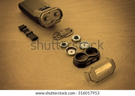 Separate elements of electric shaver on wooden table.