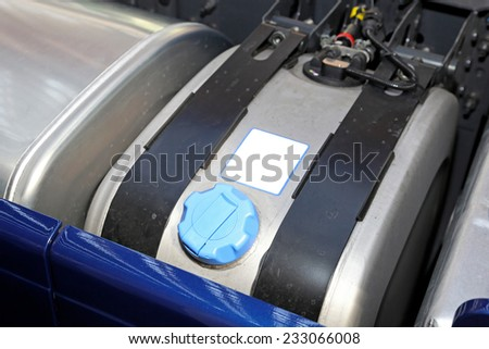 Separate tank for blue fuel additive at big truck - stock photo