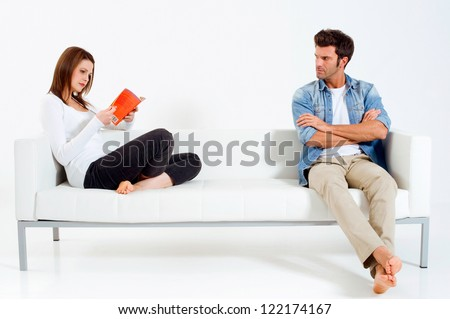 separated couple on the sofa woman reading a book